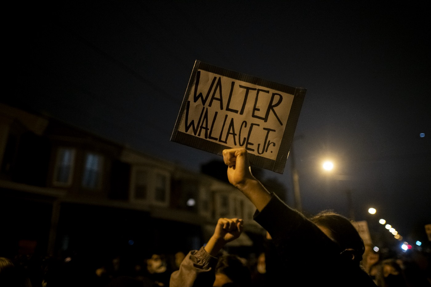 """Protestors holding a placard reading """"WALTER WALLACE JR."""" near the location where Walter Wallace Jr. was killed."""