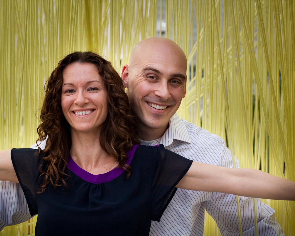 A woman and man smile in front of yellow streamers