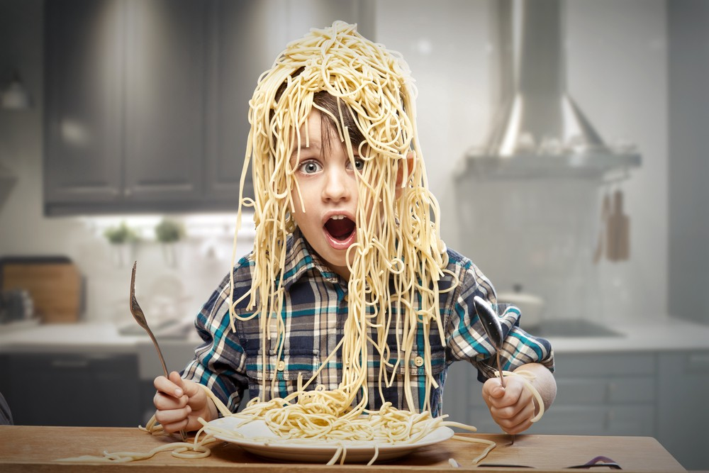 Young boy with whole head covered in spaghetti
