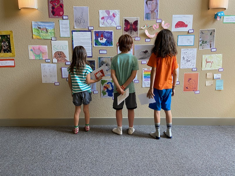 Three kids with their backs to the viewer, looking at dozens of drawings taped to the wall in front of them.