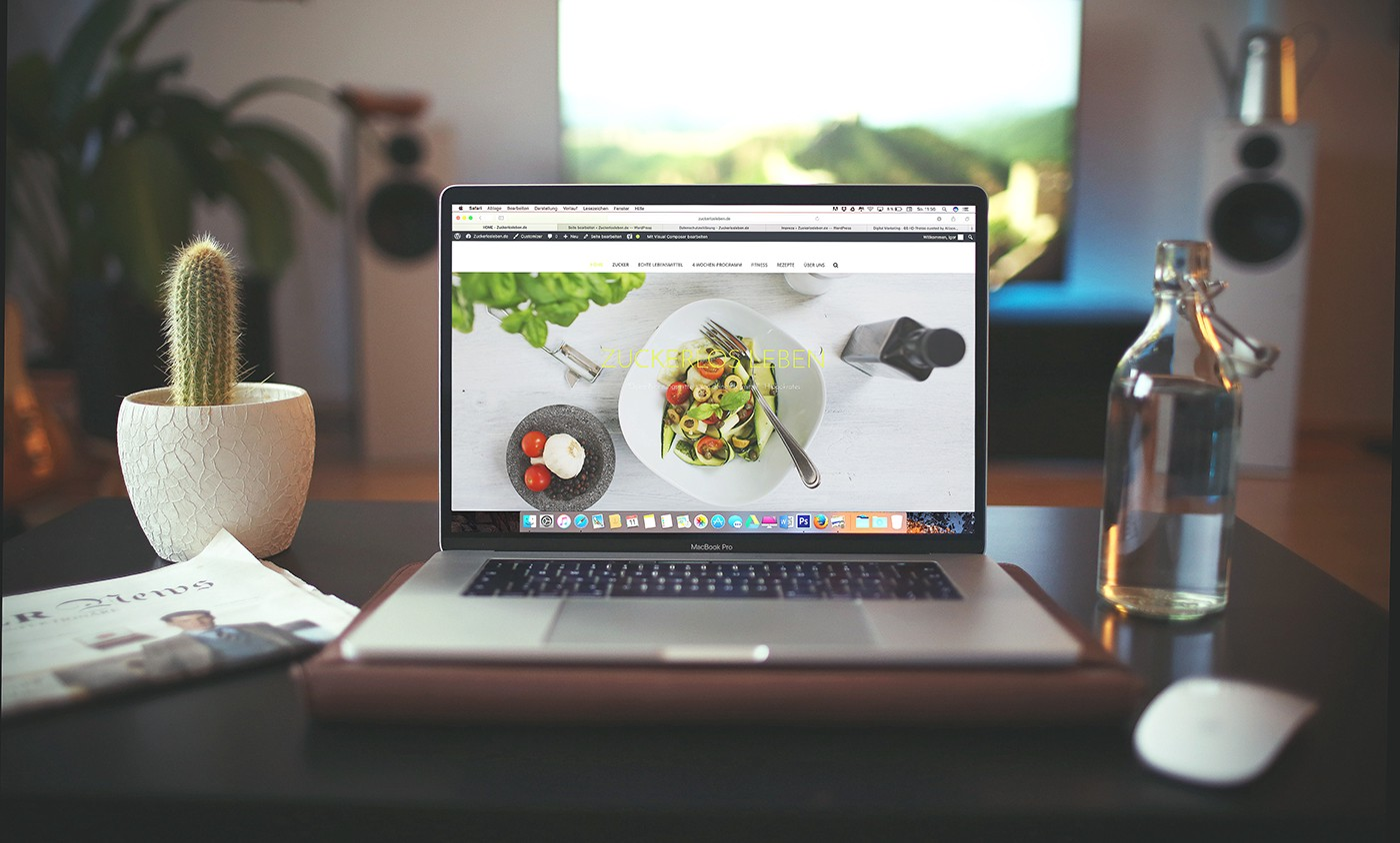 A laptop sits open on a desk. It features a food-related website in progress.