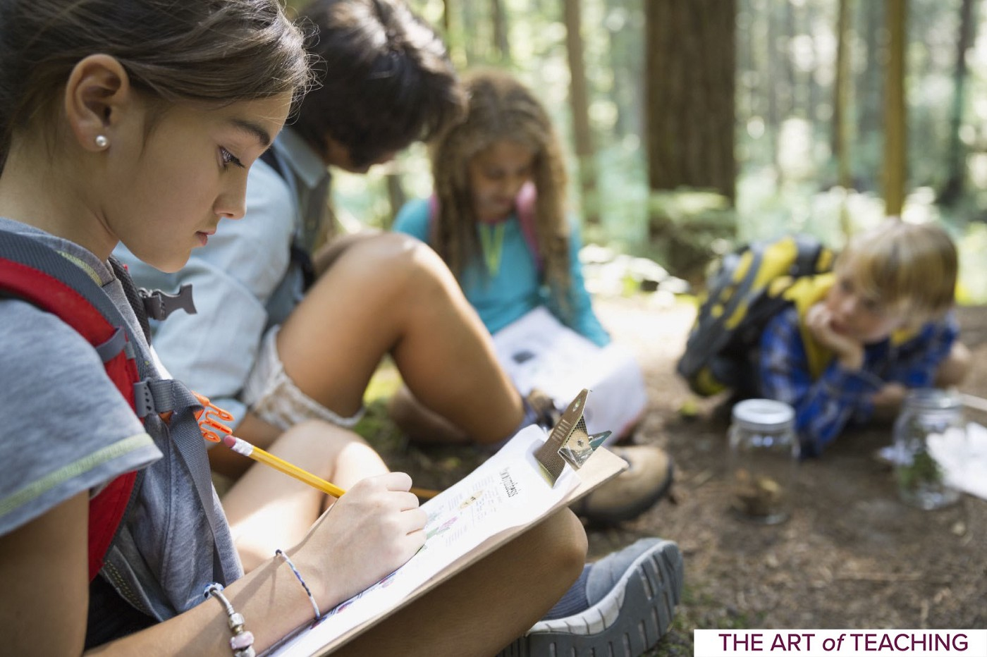 A small group of kids doing outdoor learning activities in the woods