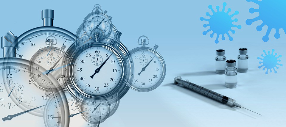 Stopwatches, vaccine ampoules, a syringe and a coronavirus molecule set against a blue background.