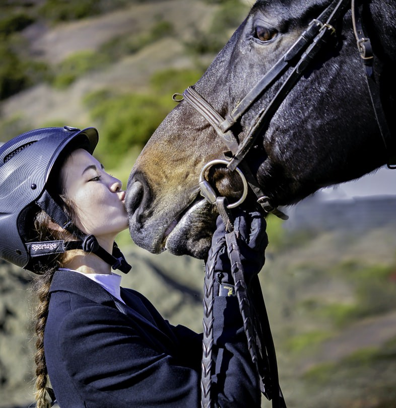 A young woman wearing a helmet showing affection to her horse's snout