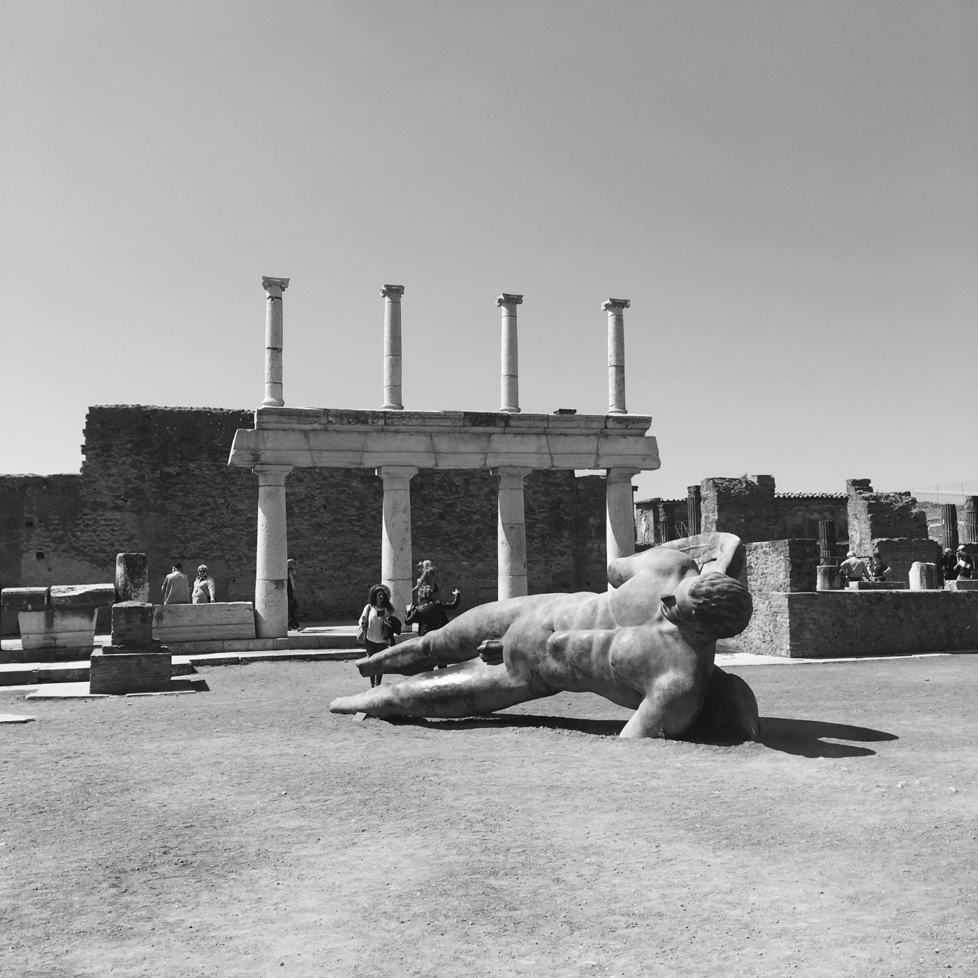 Black & white photo of a section of the excavated Forum at Pompeii. A large, modern, winged male figure is tipped on its side in front of a facade with two levels of columns.