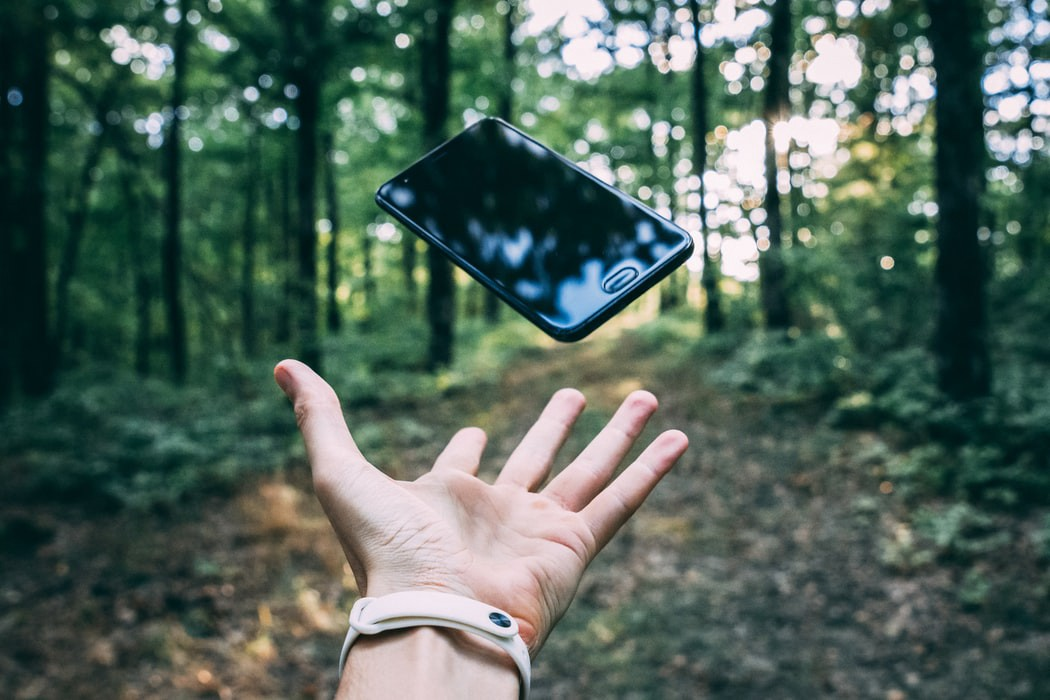 A hand throwing a phone in the air.