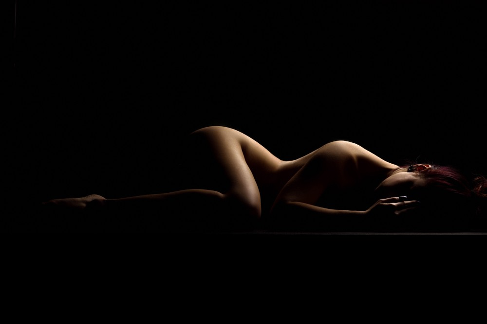Nude woman lying in bed, only viewable as a silhouette