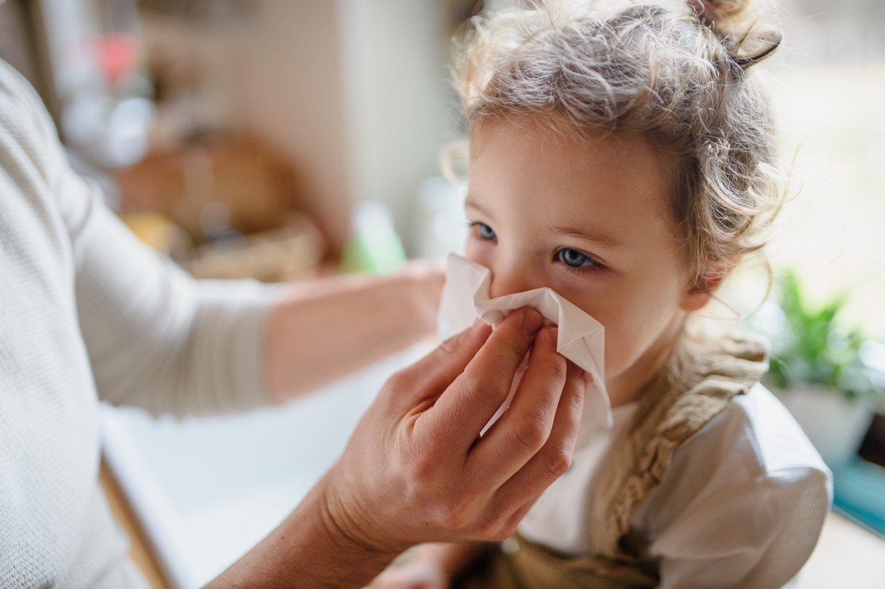 Parent with small sick toddler daughter indoors at home, blowing her nos