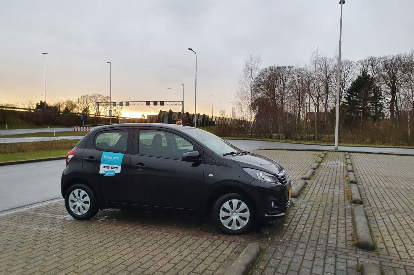 Photo of a Peugeot 108 parked in a parking lot next to a motorway. It has a sticker on it that says Juuve, the name of the rental company.