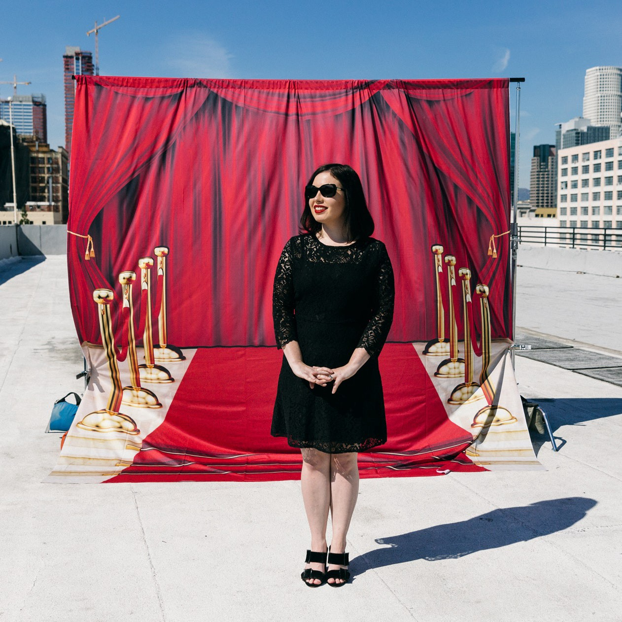 Lindsay Ellis in a black dress and black sunglasses standing with her hands figleafed together, in front of a red carpet and fake red curtain backdrop on an obviously fake set build around the city in daylight