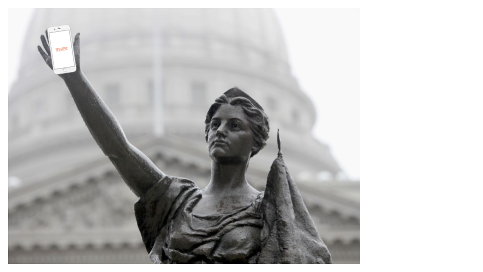 "Bronze statue (""Forward"") of woman with arm raised. Smartphone is photoshopped in her hand, screen has BenchK12 company logo."