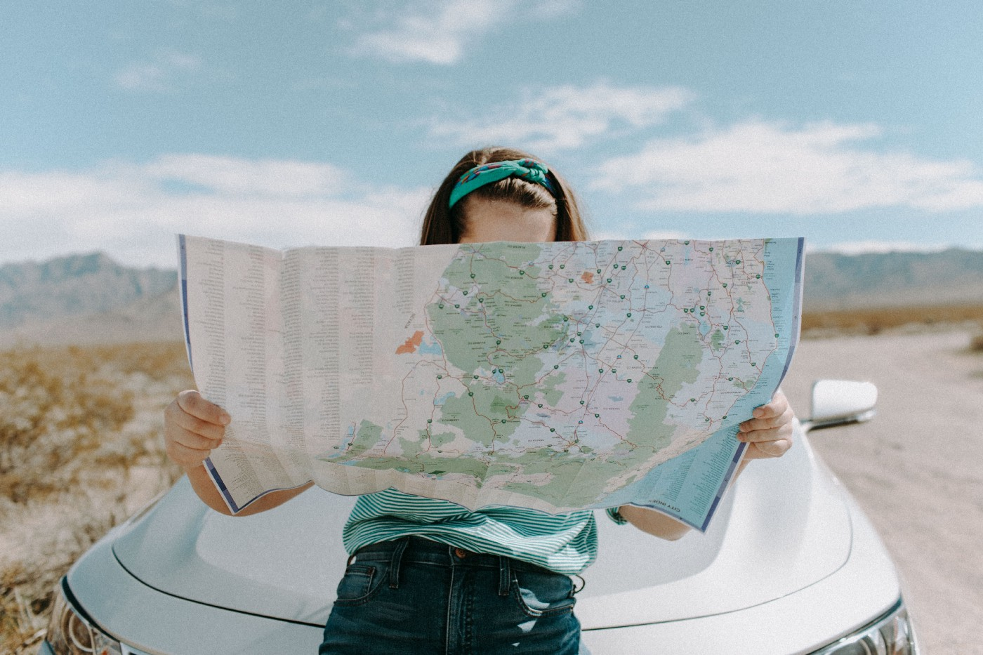 A woman in blue looking at a large map outdoors in front of a white car