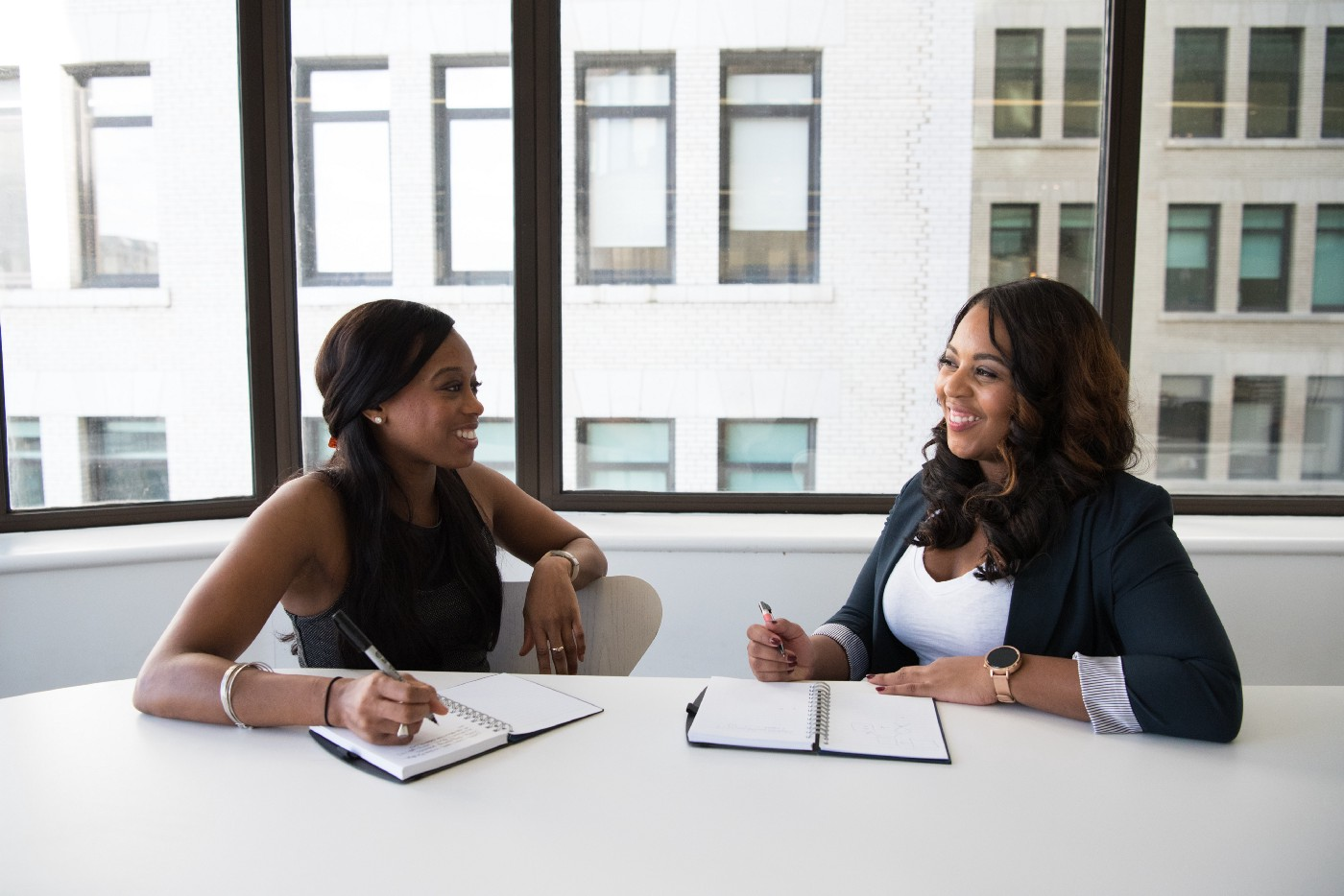 predictive analyitcs in retention management — Two women of color talking in a meeting