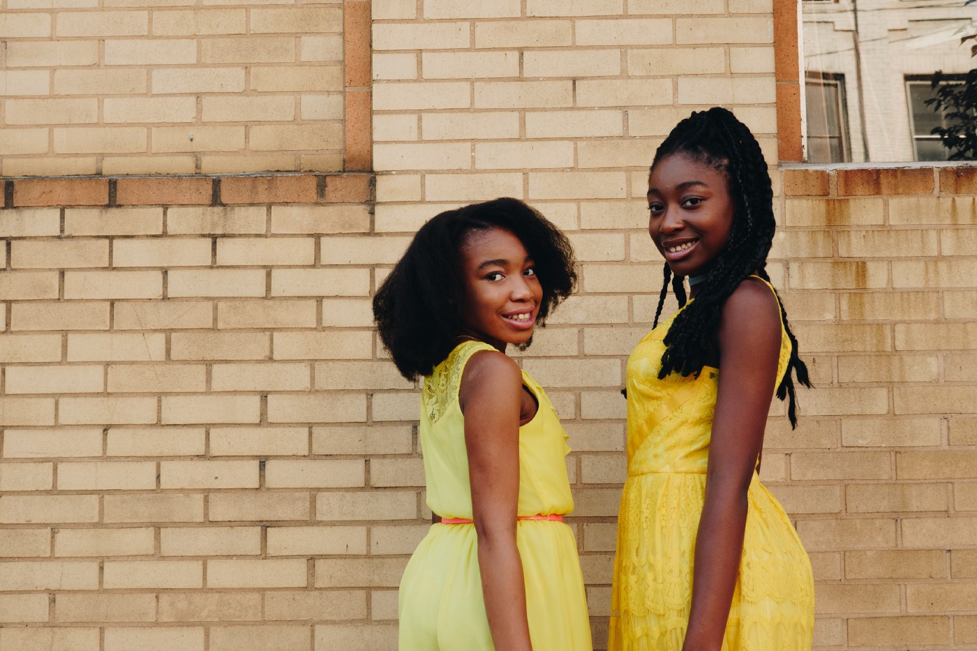 Two young black girls in yellow dresses, smiling, looking toward the photographer, standing in front of a brick wall.