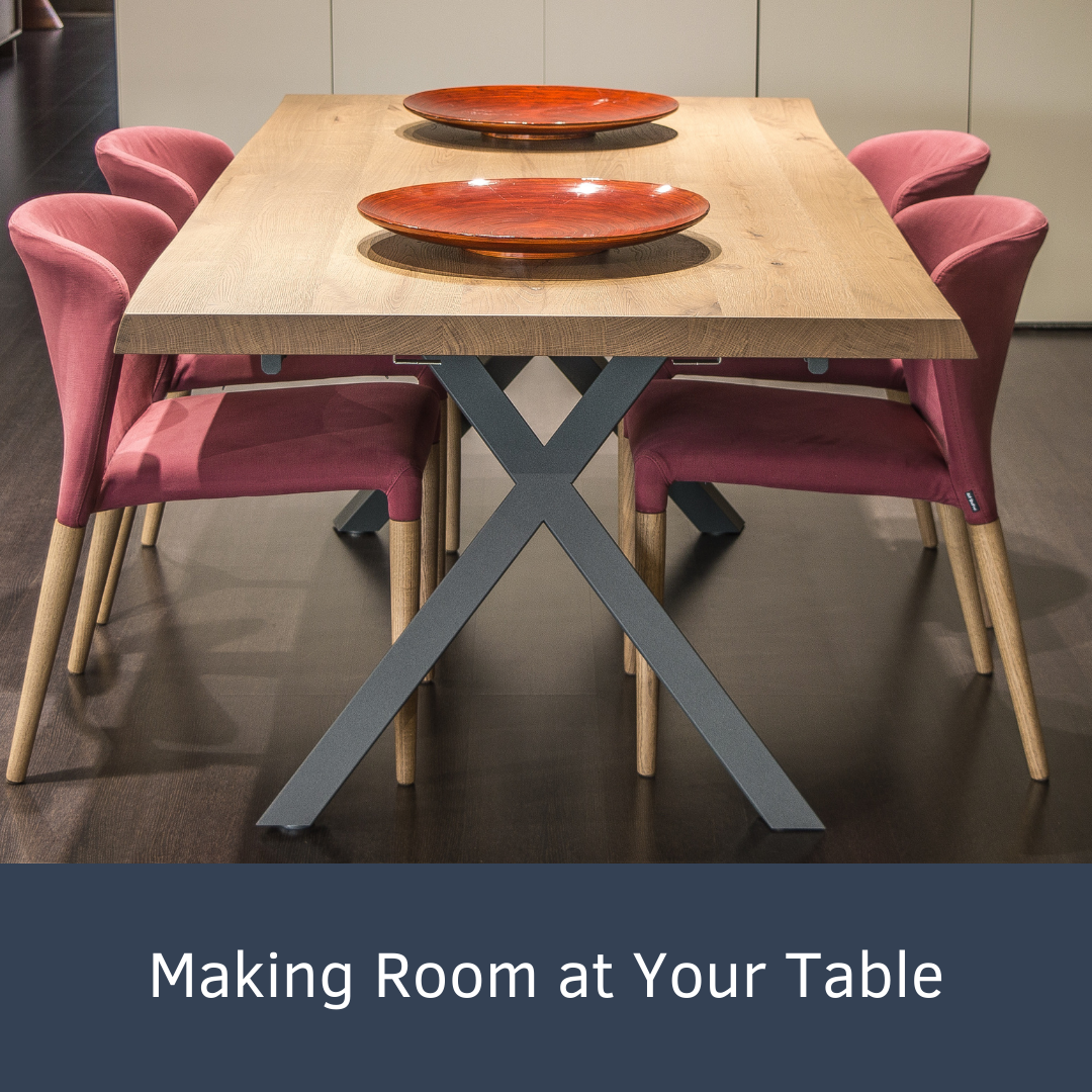 a wooden table with four soft pink chairs and two matching dark wood platters are on top.