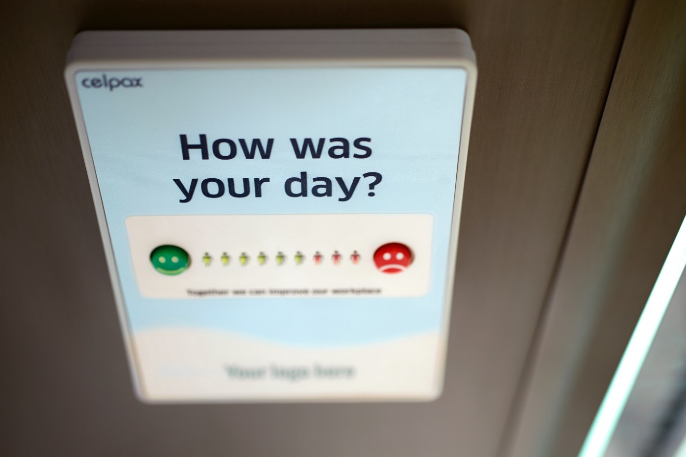 "A mobile phone is open with a prompt that says ""How was your day?"" A scale is shown ranging from a smiley face to a frown."