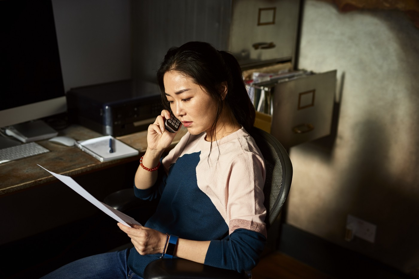 A woman looks serious as she listens on the phone while holding paperwork and sitting in an office chair.