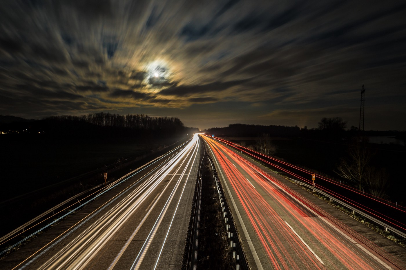 Night sky with time-lapse image of cars driving on highway.