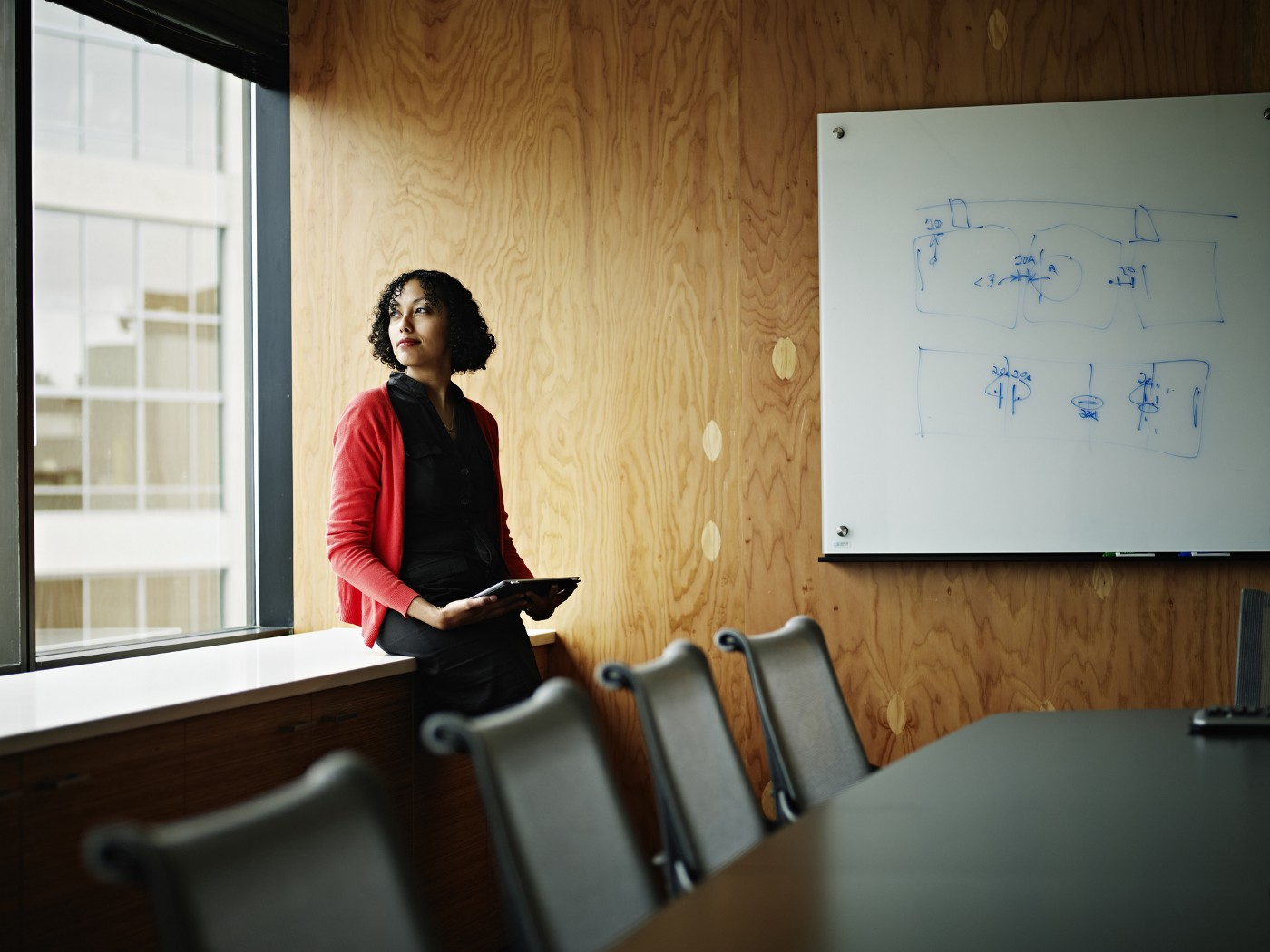 Businesswoman sitting near windows in office conference room holding digital tablet looking out.
