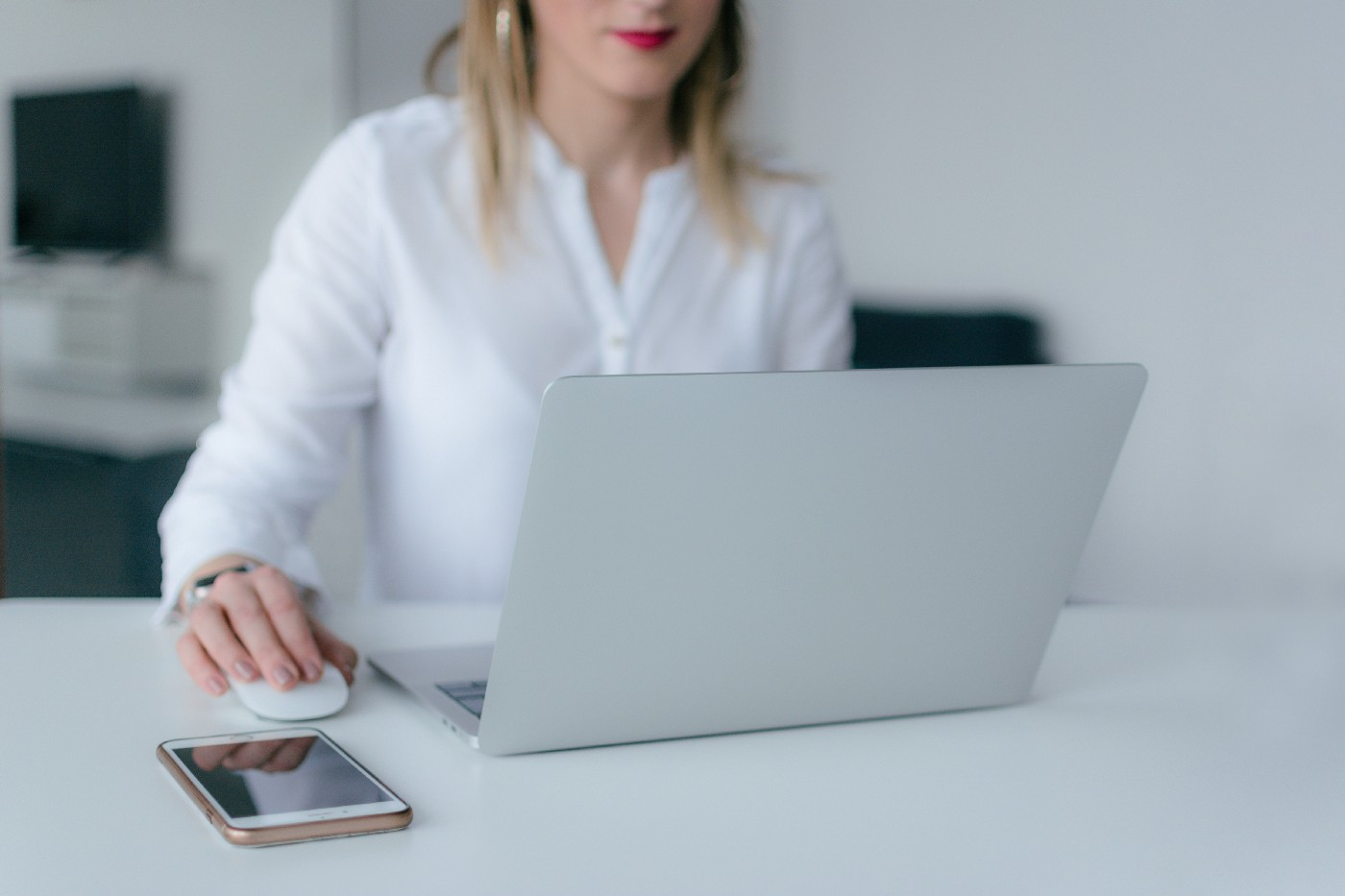 Woman siting in front of a laptop with her hand on the mouse.