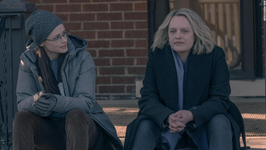 June Osborn and Emily Malek characters sitting on steps during the daytime