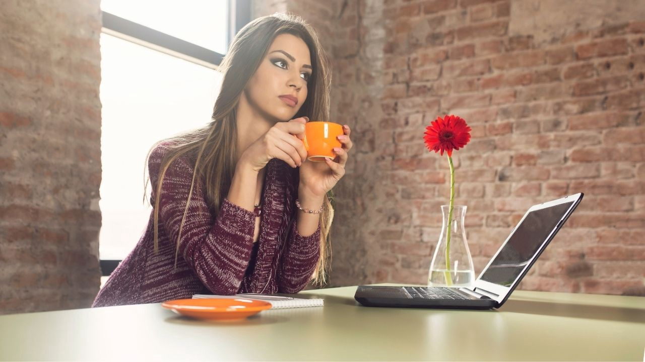 A young woman looks a little annoyed at her blog, as she is sitting at her computer, drinking coffee.