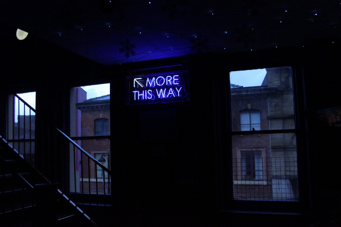 """staircase with a neon sign next to it that says """"More this way"""""""
