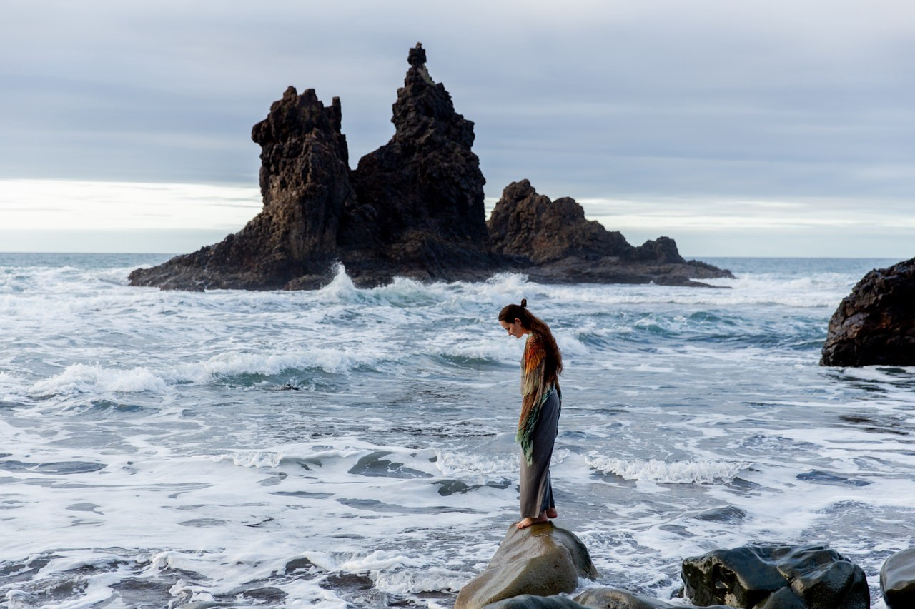 Lonely woman standing on a rocky coast surrounded by ocean