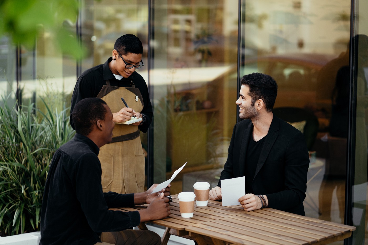 A waiter in a brown apron writes down the order of two men seated at a table with cups of coffee.