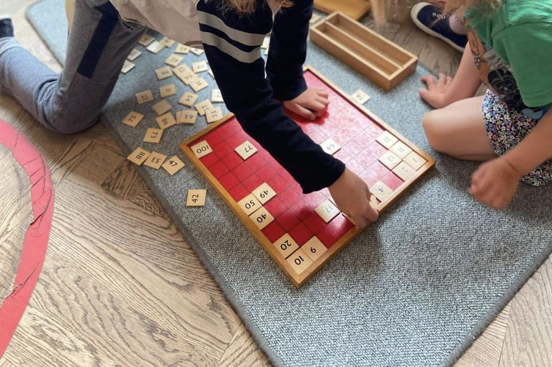 "Our oldest teaching his little sister ""The Hundred Board"" which is a key Montessori Mathematics material."