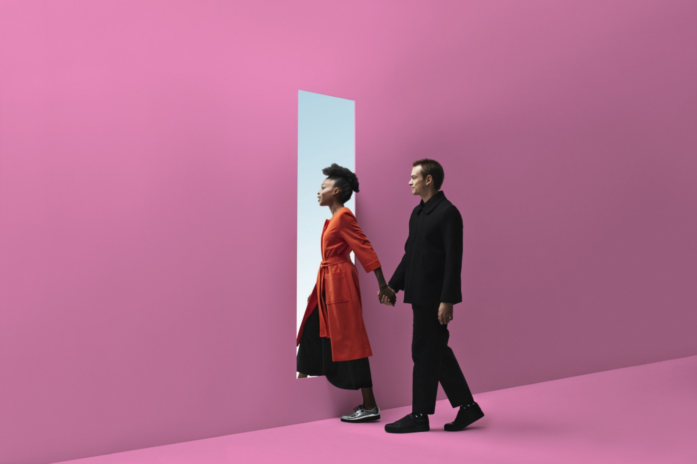 Interracial couple walking through a door in a pink wall, holding hands.