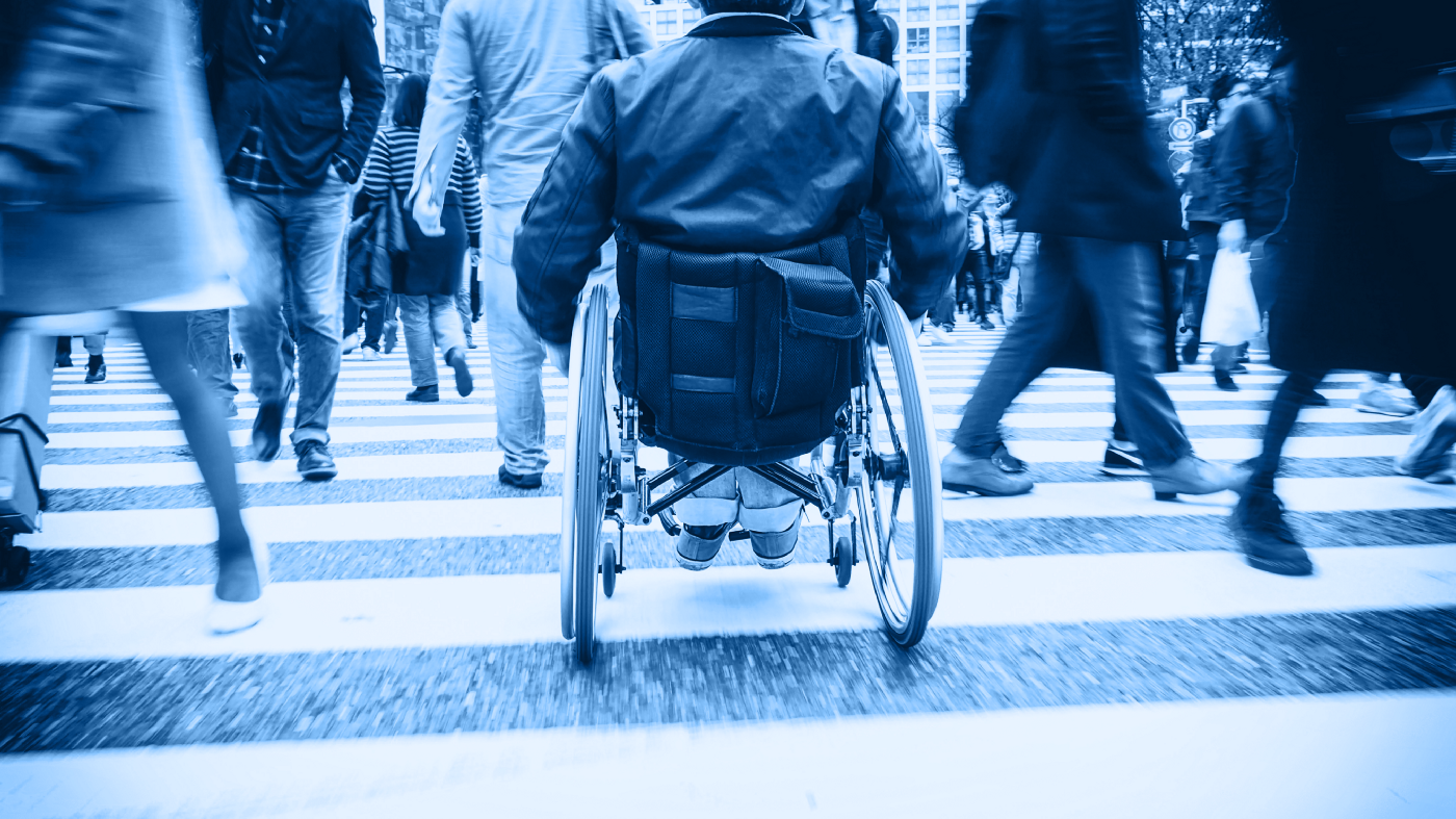 A person in a wheelchair using a crosswalk on a busy city street.