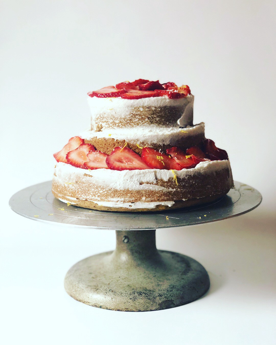 A layered cake on a silver cake stand — the cake is golden brown with lightly applied white icing and strawberries.
