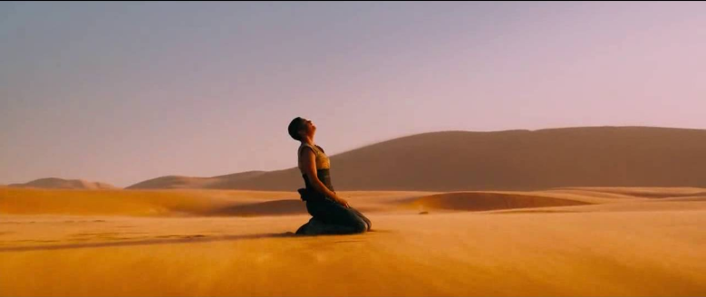 Furiosa from Mad Max Fury Road kneeling and screaming in the desert