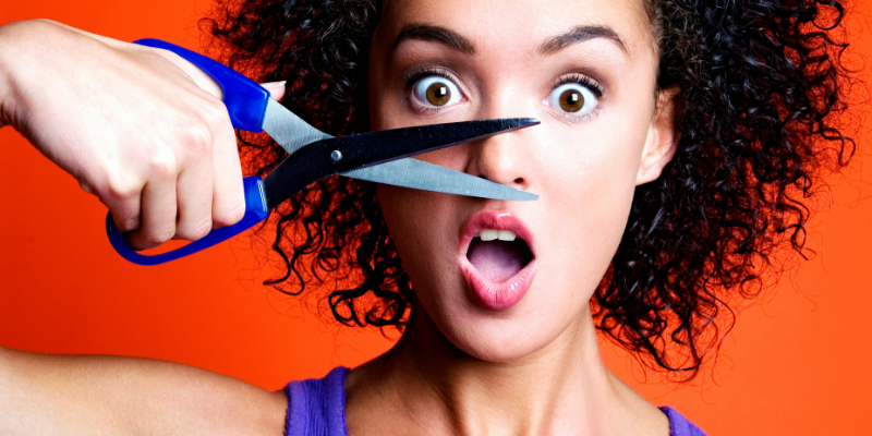 Woman pretending to cut her nose with a pair of scissors — Five English Words That Don't Make Any Damn Sense