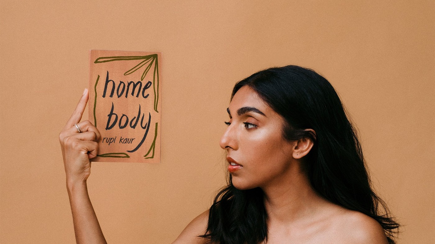 Poet Rupi Kaur holding her newest poetry book, Home Body