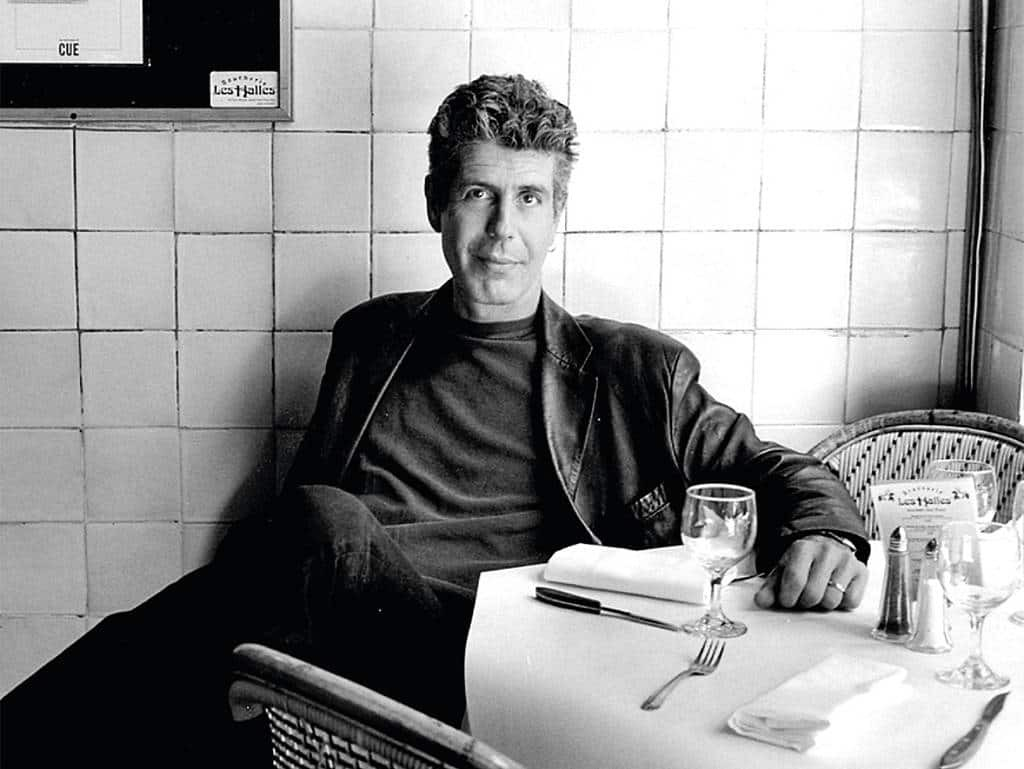 A black & white photo of Anthony Bourdain sitting at a restaurant table.