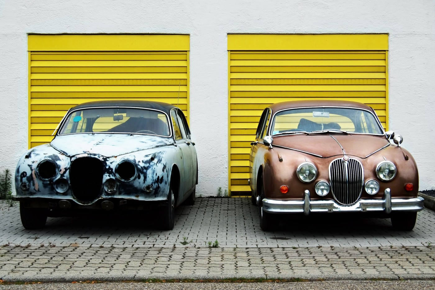 Two car side by side in front of yellow doors. Left car is old and dilapidated. Right car is a gorgeous classic.