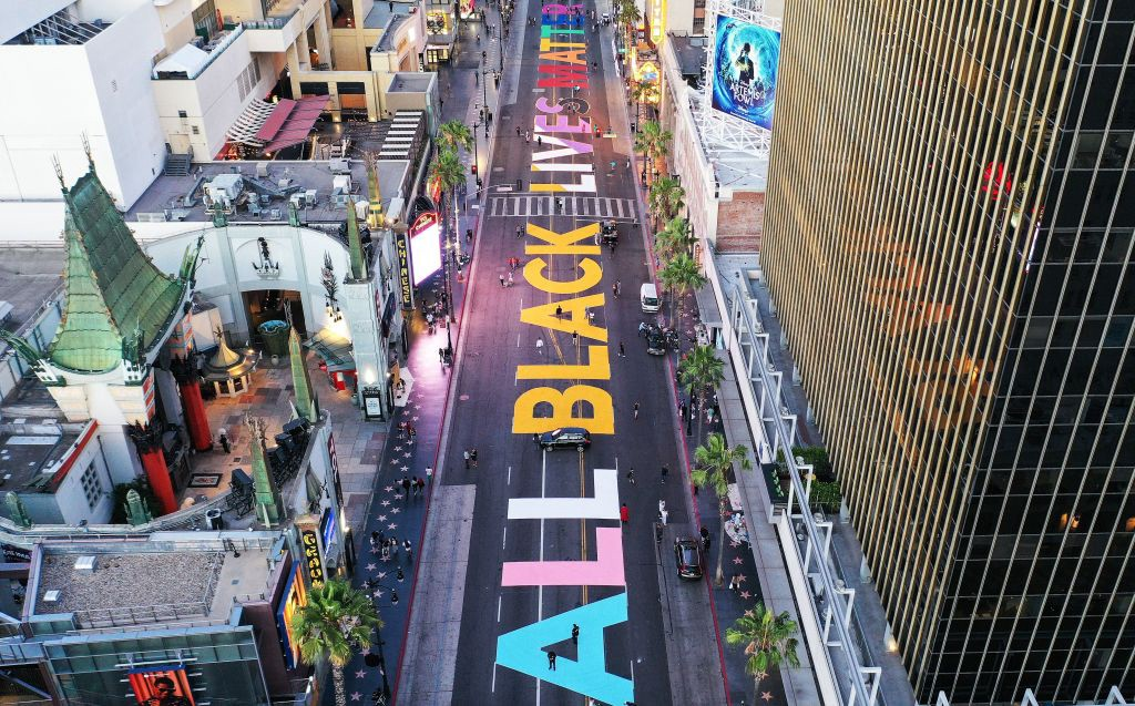 "An aerial photo, presumably taken by drone, of protests in LA. ""ALL BLACK LIVES MATTER"" is painted on the road."
