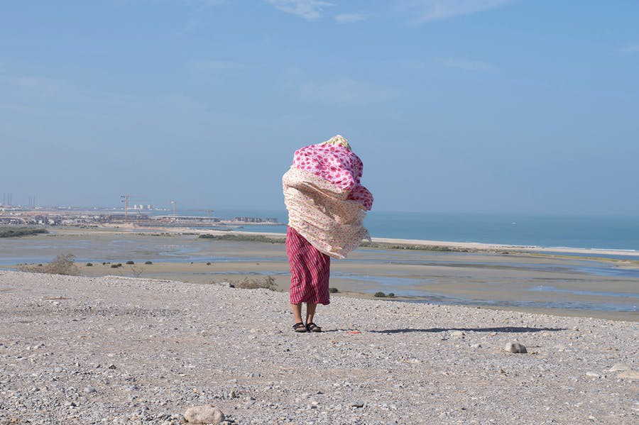 Um Al Naar blows in the wind, standing on gravel with a blue sky behind her.