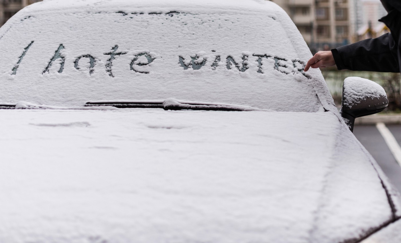 """""""I hate winter"""" written on snow covering a car."""
