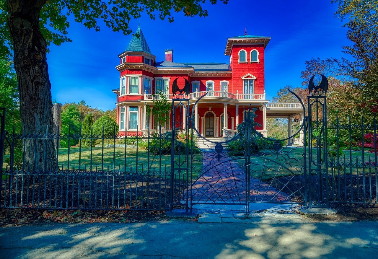 Home of Stephen King, an old Victorian-style red house surrounded by a wrought iron fence with bats, spiders, and dragons.