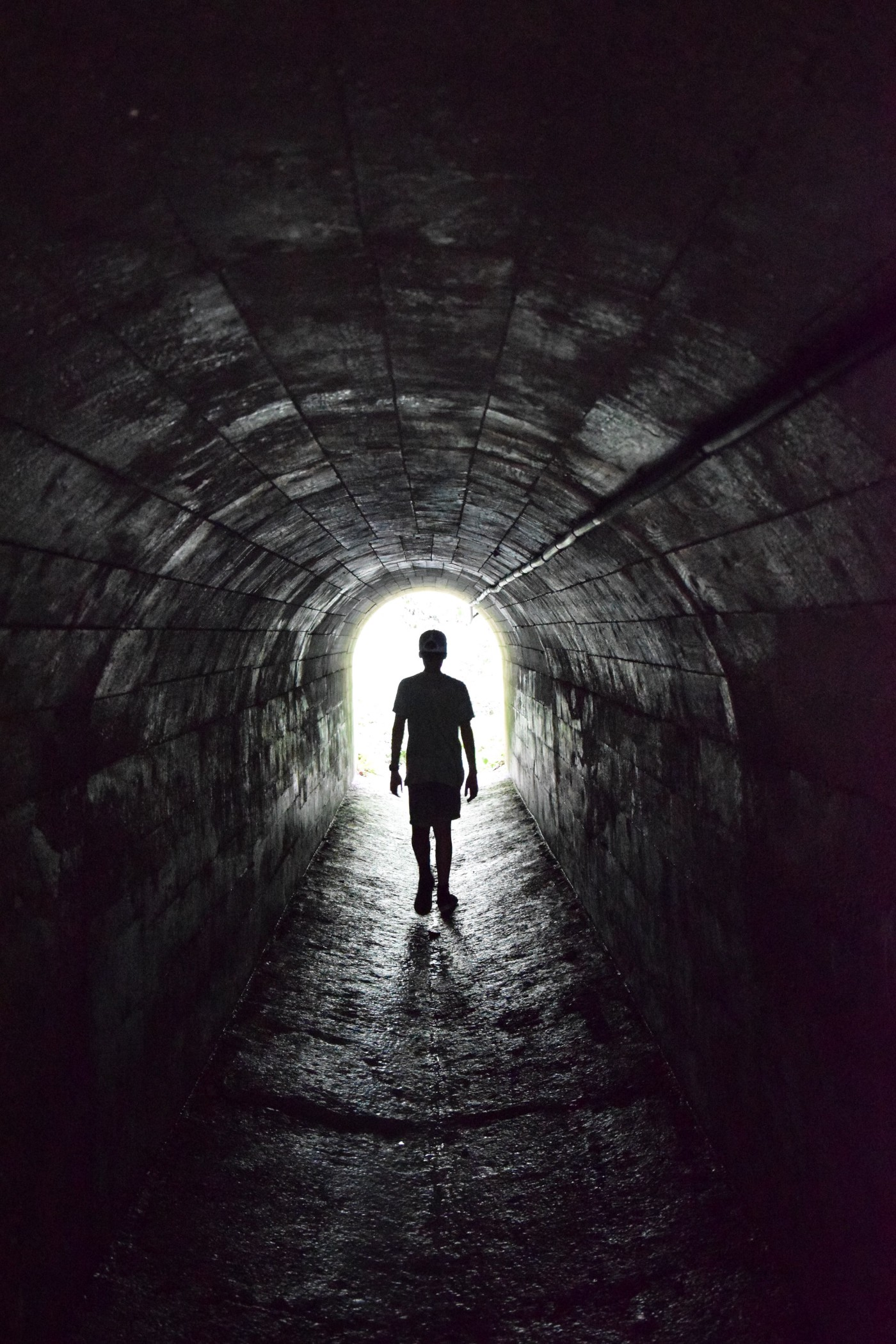 Person walking towards the light at the end of a tunnel