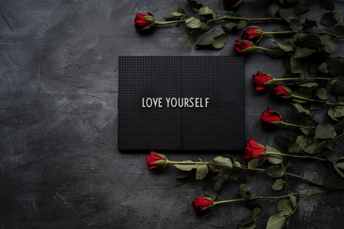 A black envelop that reads love yourself surrounded by red roses.