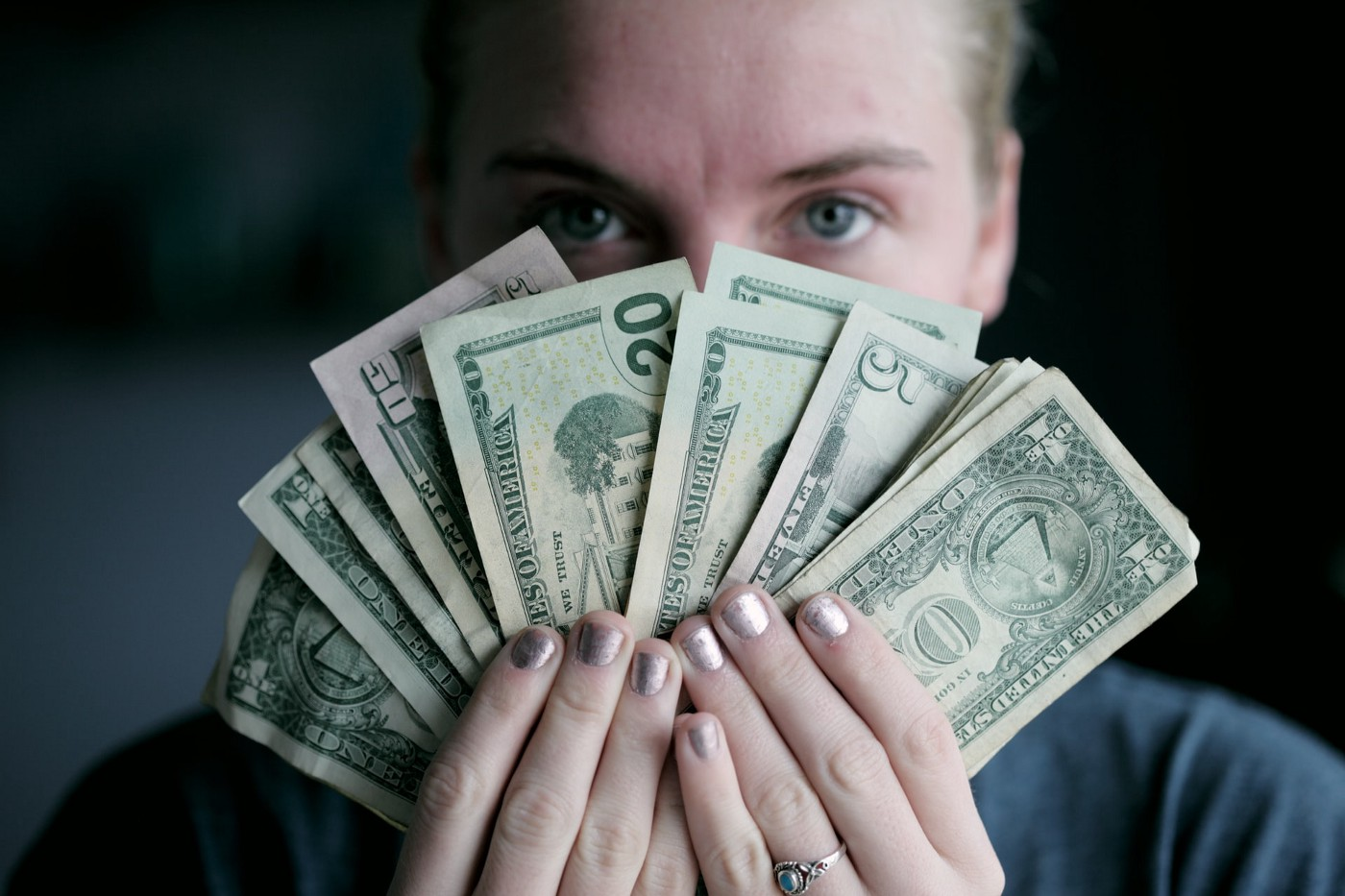 Woman holding cash.