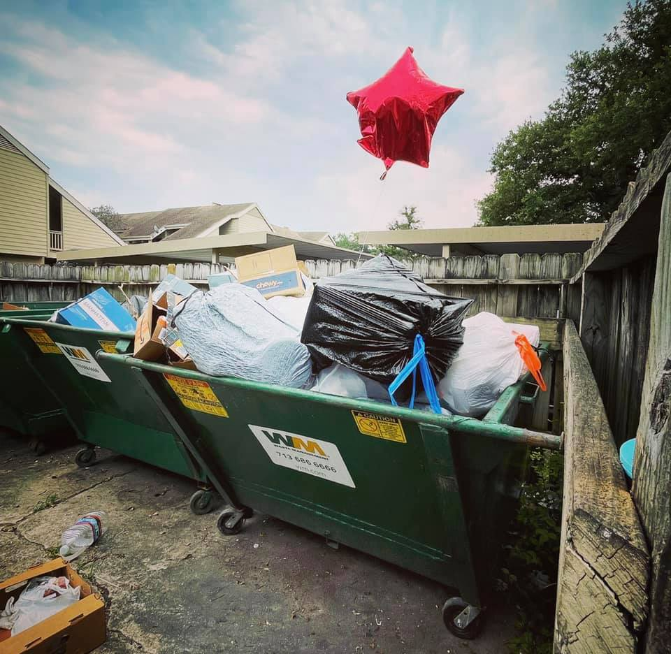 A red star shaped mylar balloon floats above an overfilled dumpster.