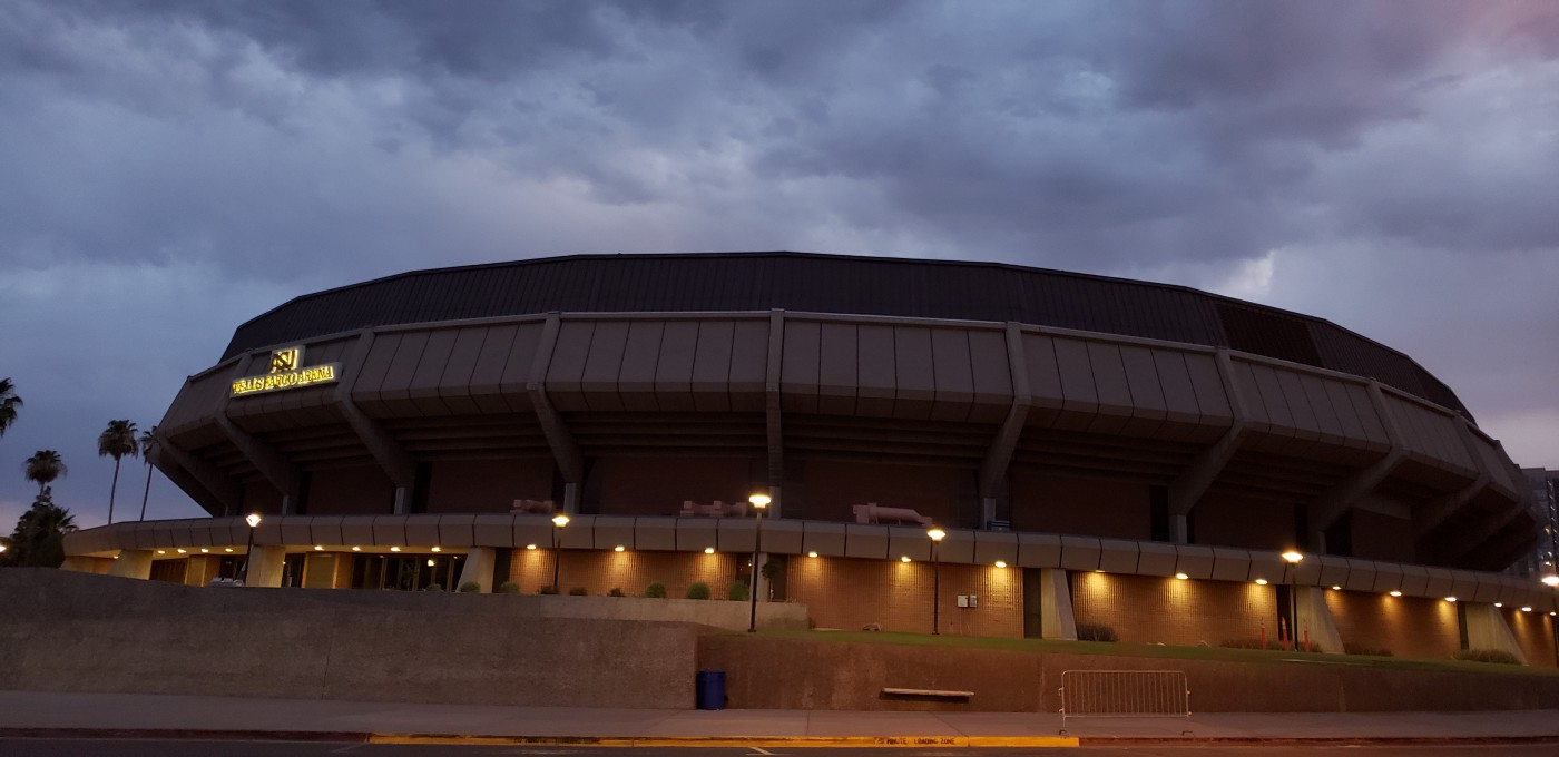 Arizona State Univerity arena at dusk with illuminating lights with a cloudy background