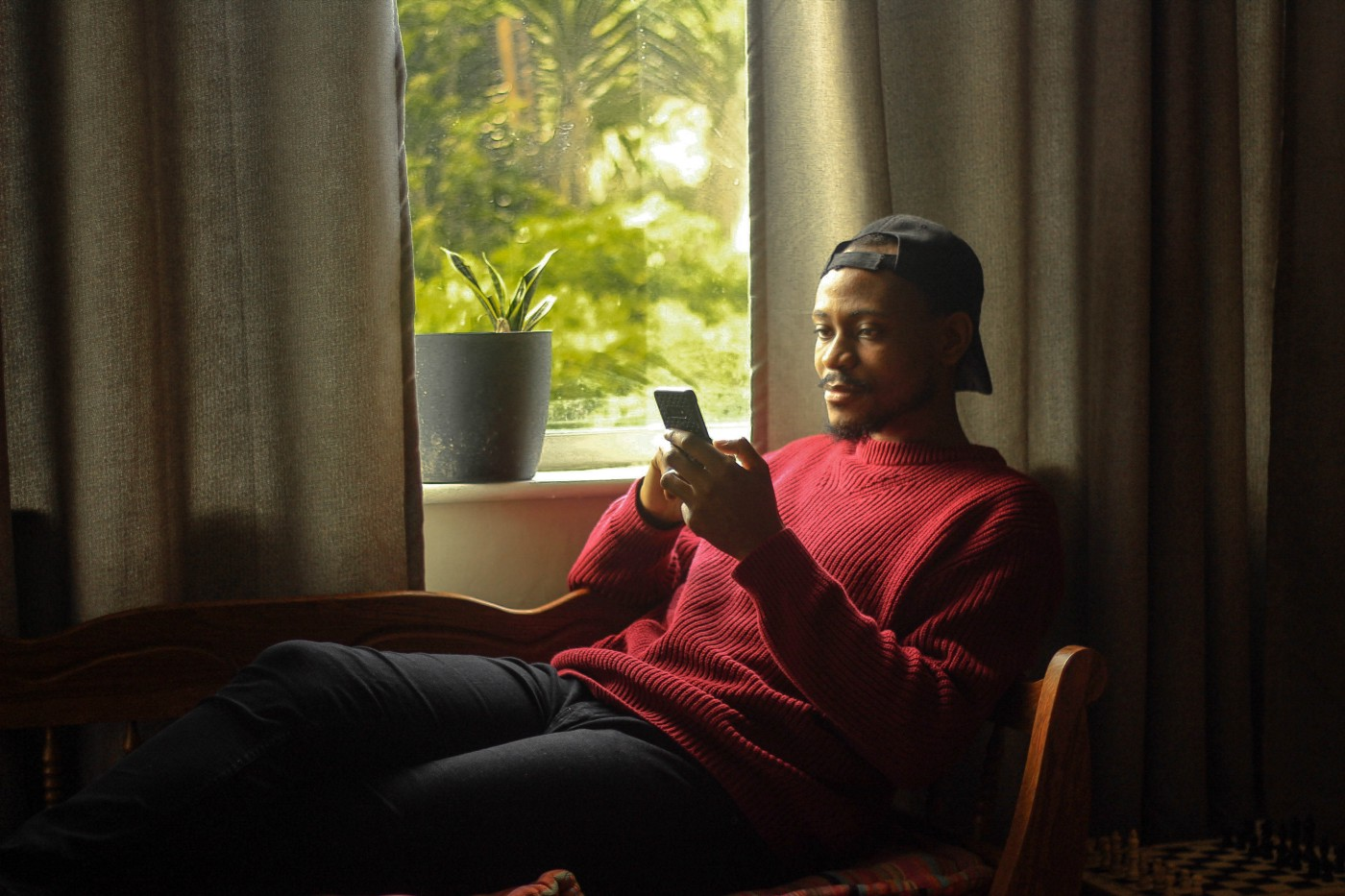 Black man rests by his window while looking at his phone.