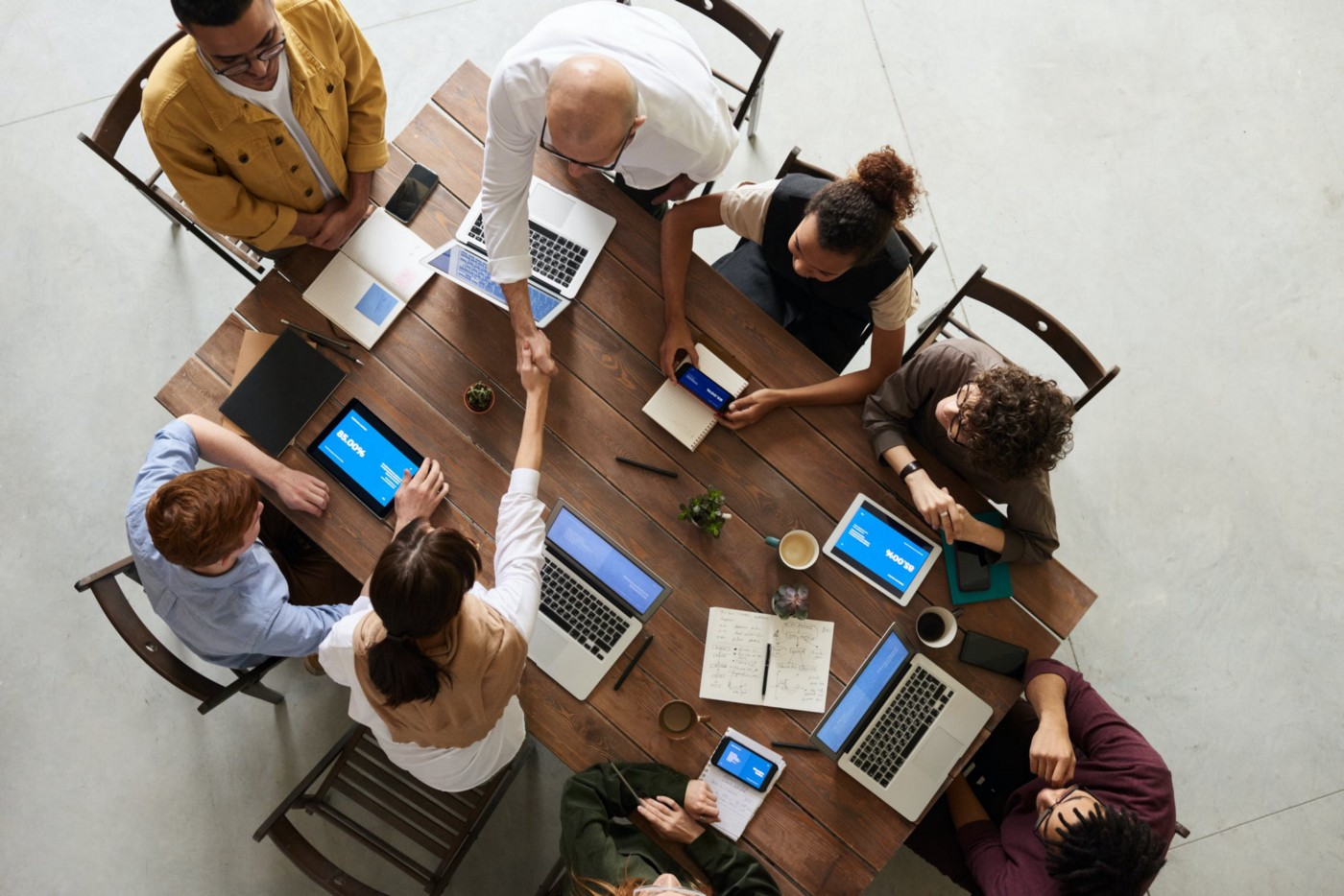 Teamwork image of a group of people in a meeting working together on a wooden table with computers, tablets and smartphones