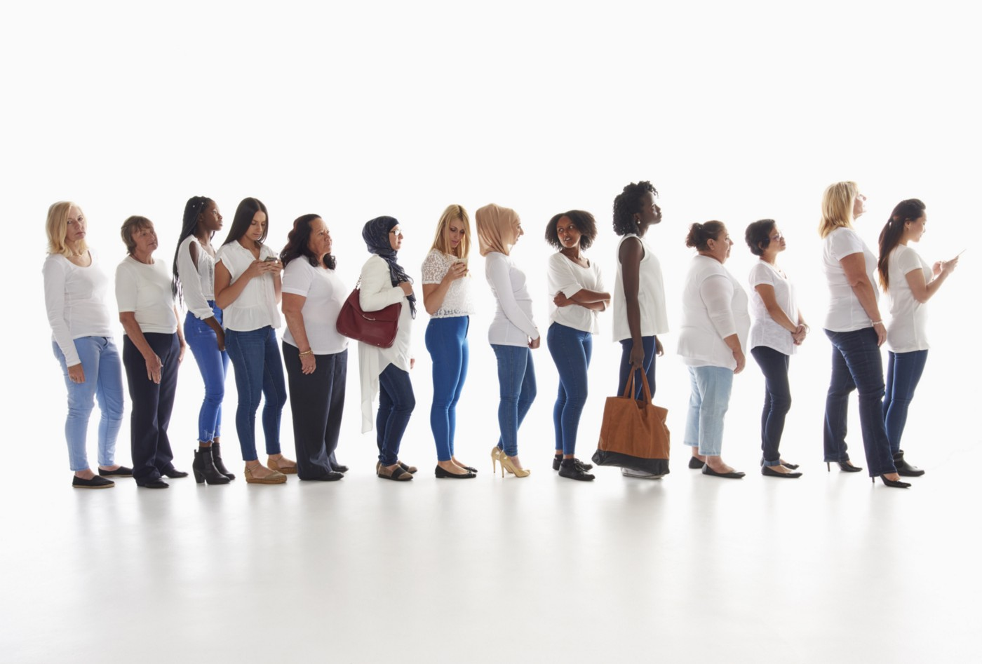 A diverse group of women standing in line. They are wearing different styles of blue denim jeans and white shirts.